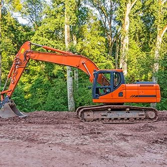 Orange crawler excavator standing in the woods